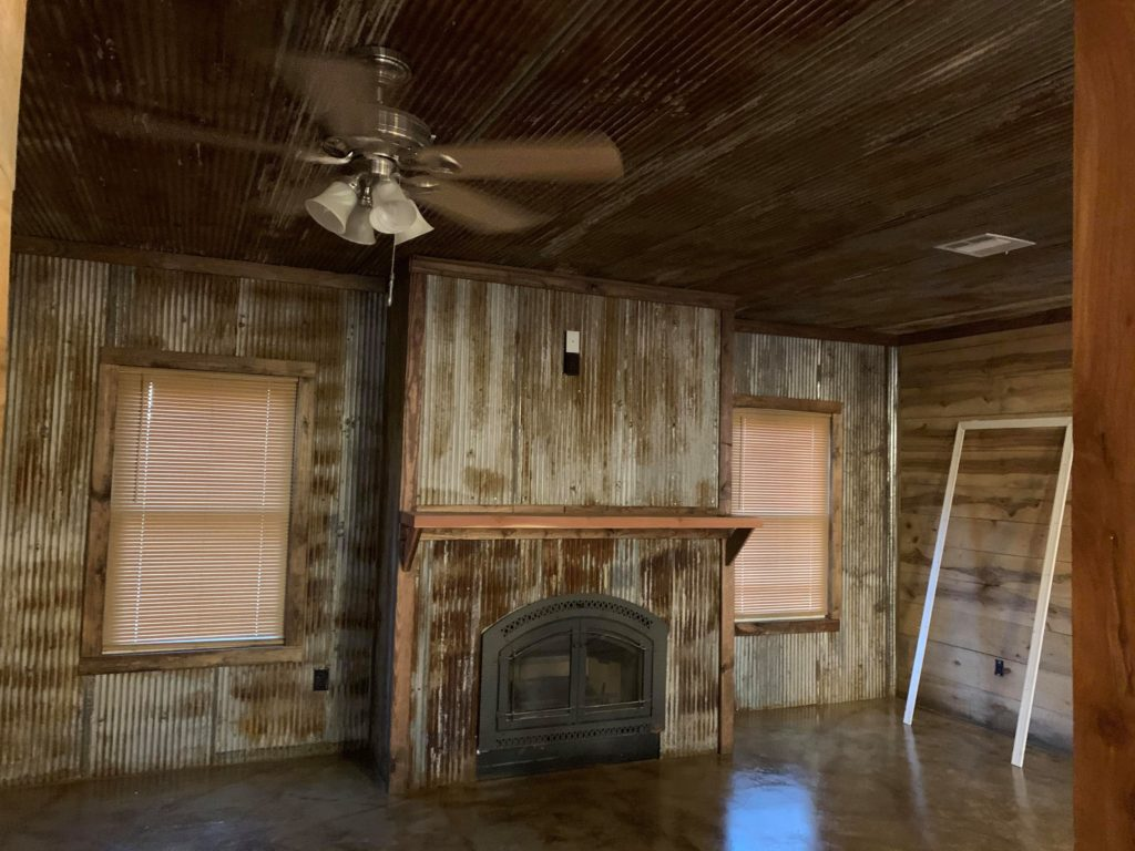 Reclaimed corrugated tins for the ceiling, fireplace, and living room walls