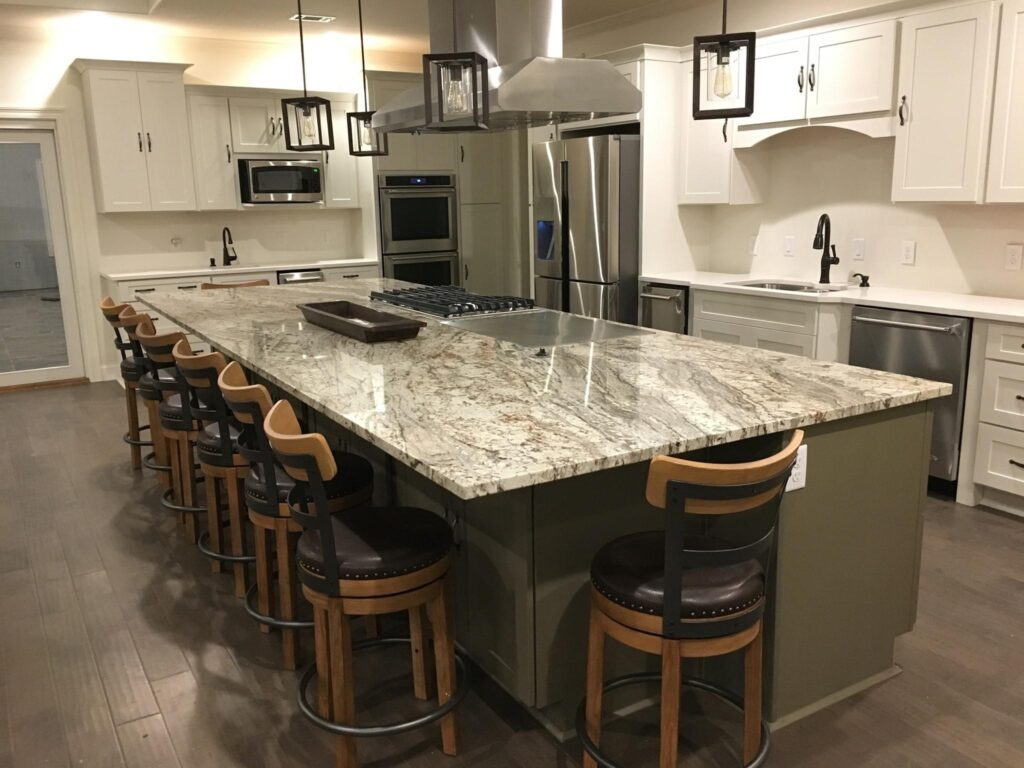 View of kitchen granite counter-top with seating, white cabinets, and stainless steel appliances