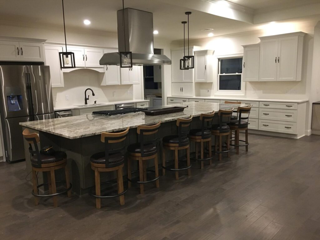 View from another angle of kitchen granite counter-top with seating, white cabinets, and stainless steel appliances