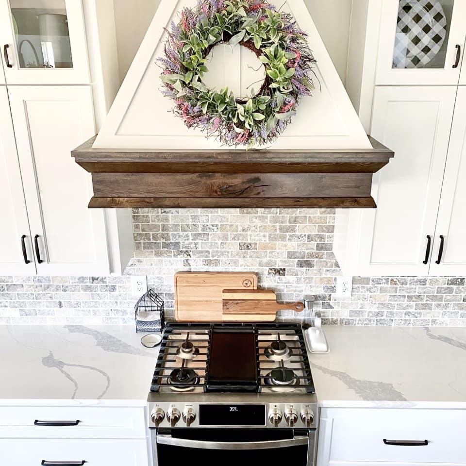 Decorative wreath on kitchen exhaust vent and top view of the stainless kitchen stove and marble countertops
