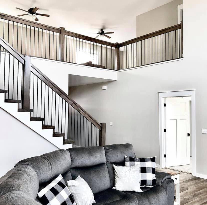 Stairs to the second floor with dark brown stained wood railings