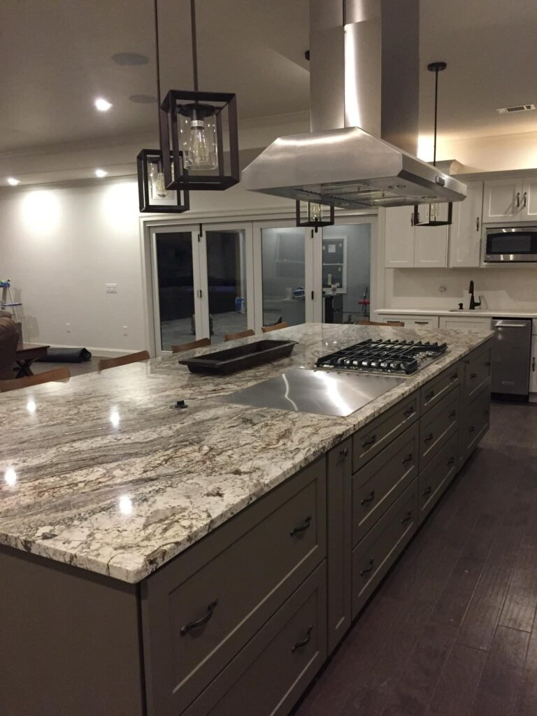 Granite-covered kitchen island with stove-top and grill