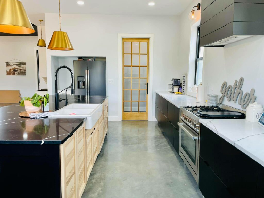 Kitchen image of farmhouse sink, gas range, and door to the laundry room.