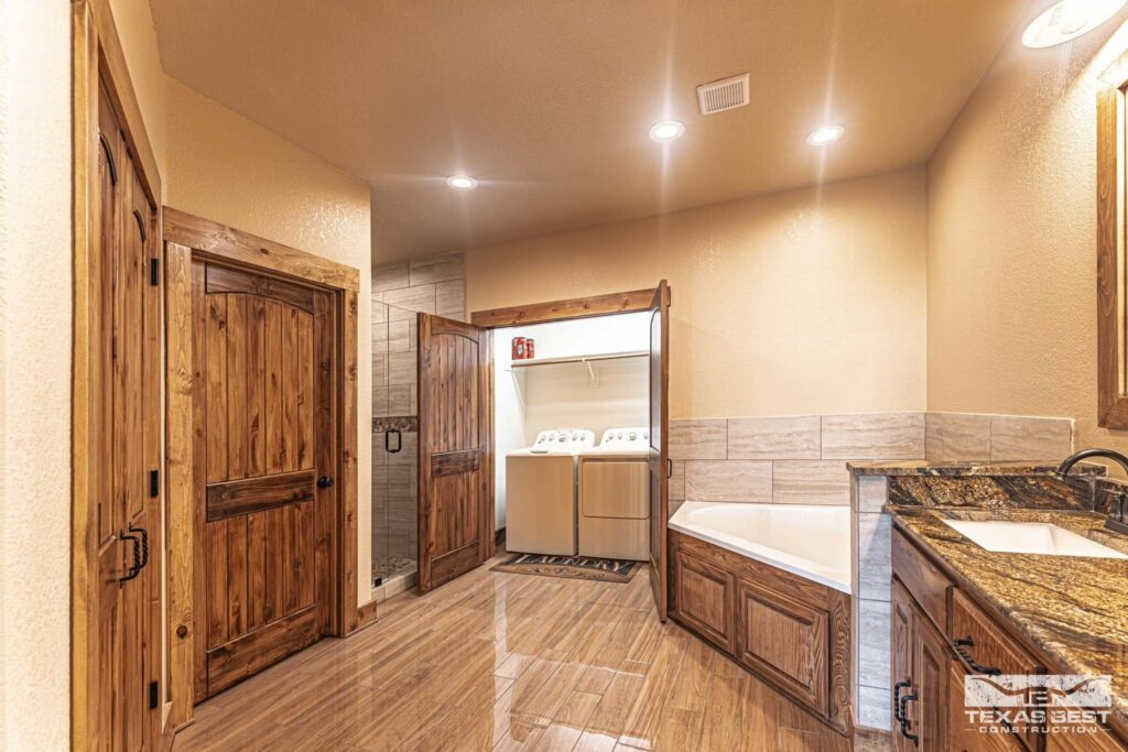 Master bathroom with large tub and laundry closet