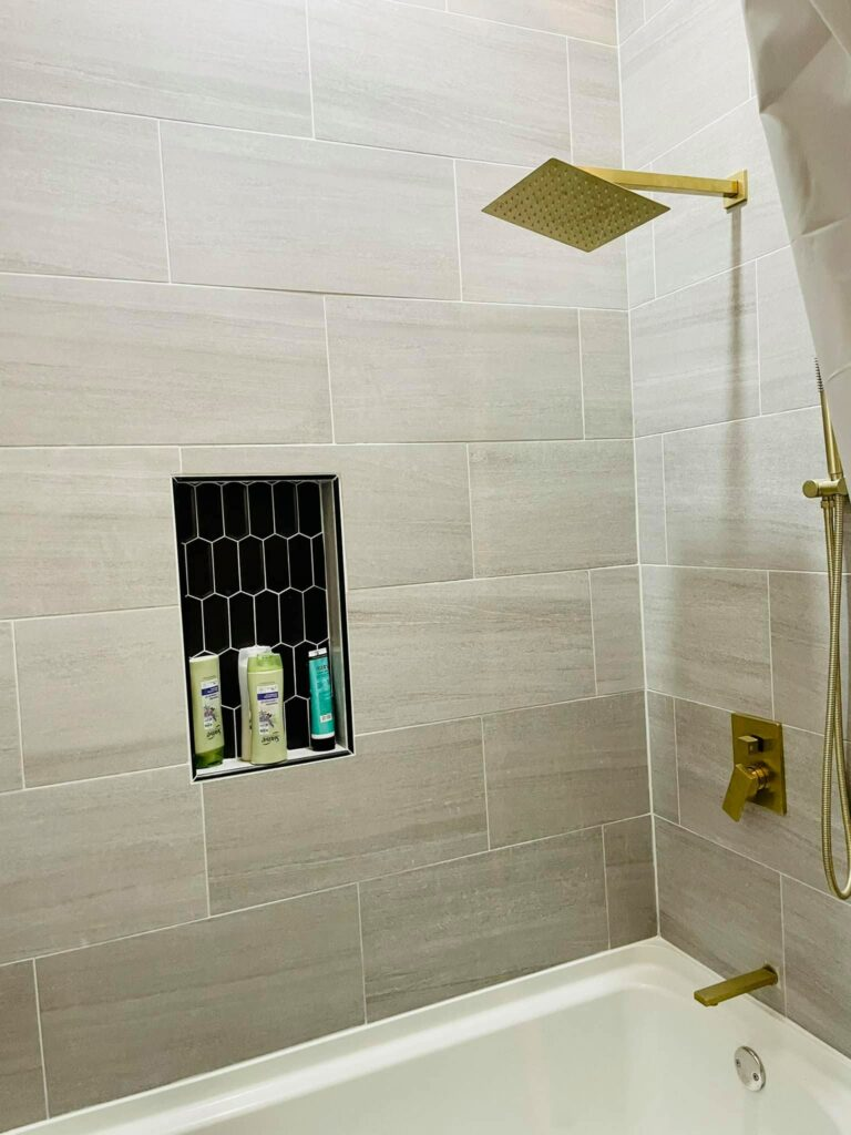 Sandy colored tile shower with gold fixtures.
