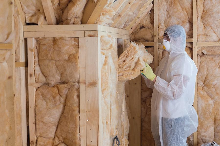 worker installing batting insulation