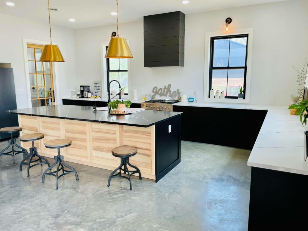 Kitchen with black lower cabinets and a large island.