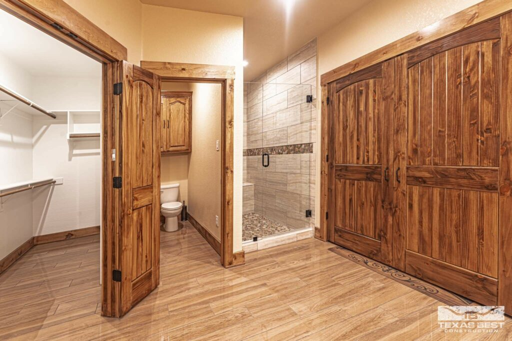 Bathroom with laundry closet, walk-in closet, and walk-in shower