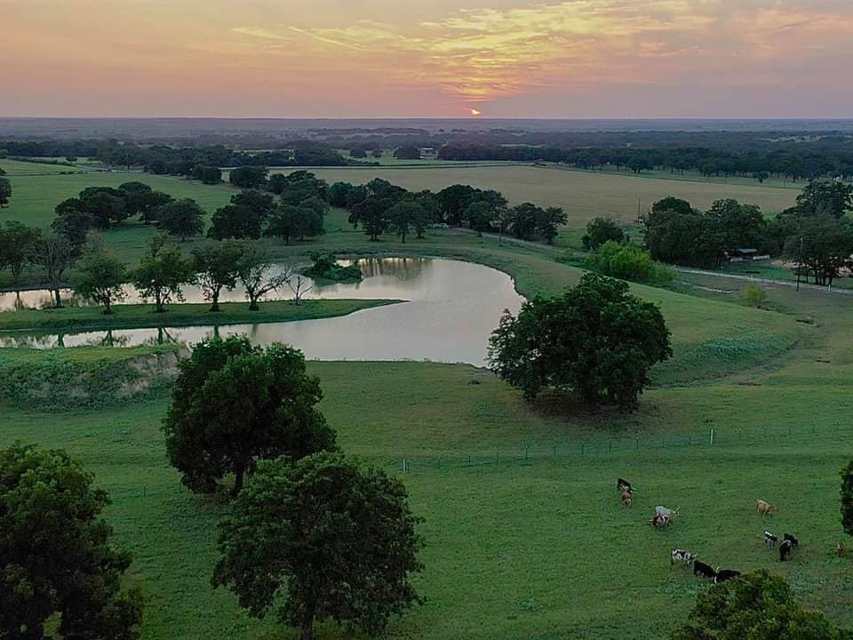 Unique Texas Hillside Barndominium with a Gorgeous View of this pond that reflects the sunset